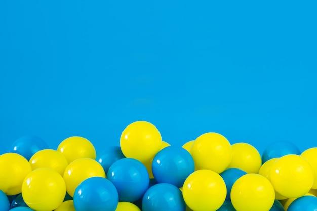 Bolas de plástico amarelas e azuis na piscina da sala de jogos