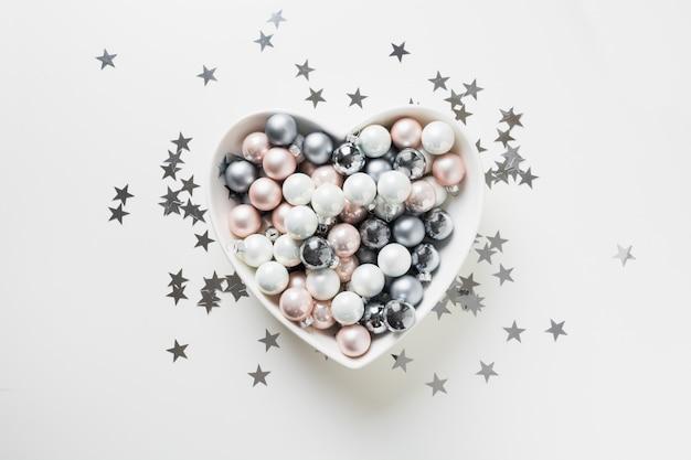 Bolas de prata brancas, rosa, cinza de natal em forma de coração em fundo rosa decorado conceito de estrelas de confetes.