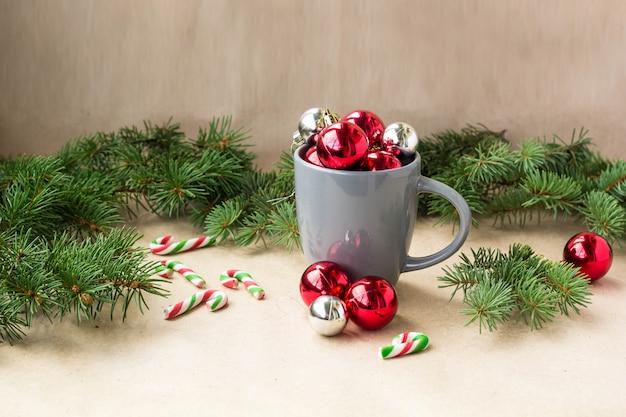 Bolas de prata e vermelho decorações de natal em copo com árvore de abeto