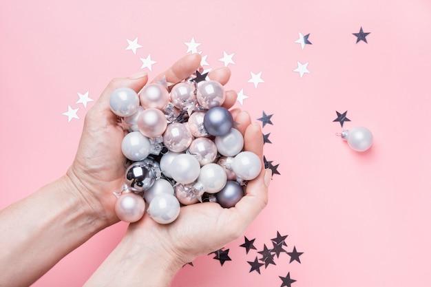 Bolas de prata pastel coloridas de natal nas mãos femininas na rosa.