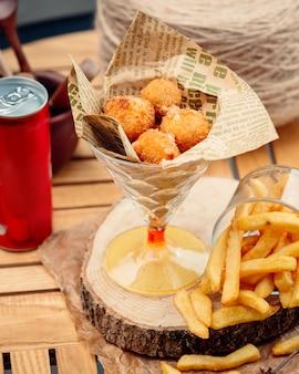 Bolas de queijo com batatas fritas na mesa