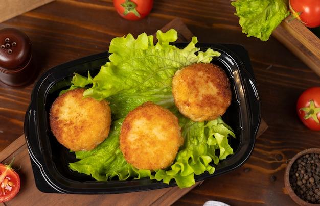 Bolas de queijo frito assado com batata recheada com queijo e carne takeaway