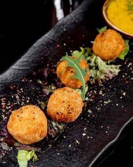 Bolas de queijo vista lateral com especiarias e ervas aromáticas