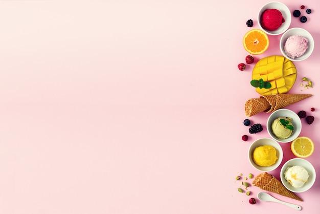 Bolas de sorvete em tigelas, cones de waffle, bagas, laranja, manga, pistache na rosa chique gasto. coleção colorida, apartamento leigo, conceito de verão, vista superior