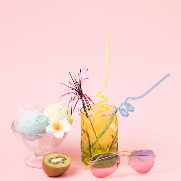 Bolas de sorvete na taça perto de óculos escuros e vidro com varinha ornamental e palhas