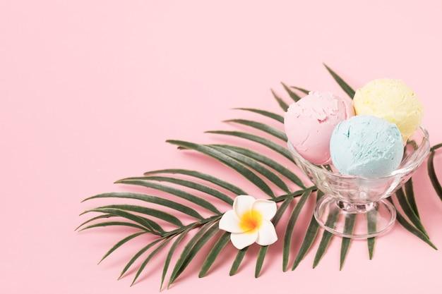 Bolas de sorvete na tigela de vidro perto de folhagem de plantas e flores
