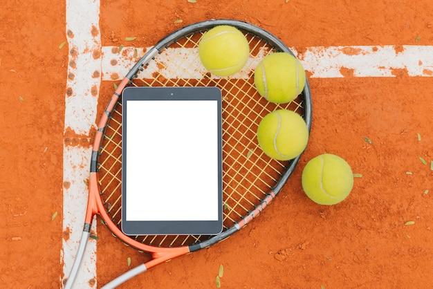 Bolas de tênis com raquete e tablet