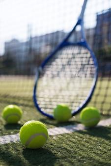 Bolas de tênis de baixo ângulo e raquete no campo