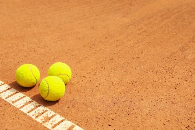 Bolas de tênis verdes claras na quadra de saibro