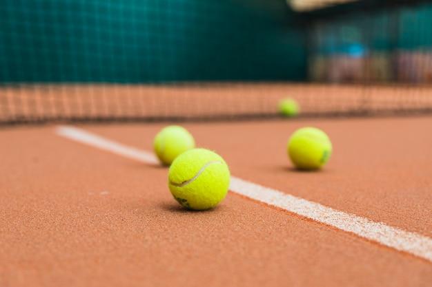 Bolas de tênis verdes na quadra perto da rede