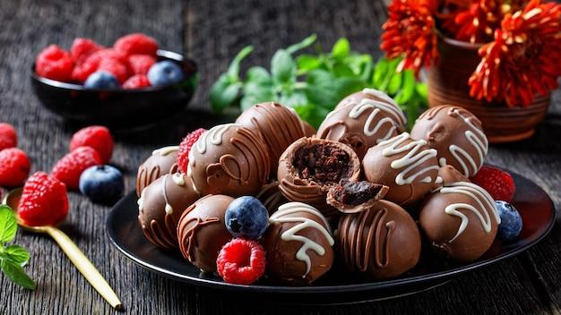 Bolas de trufas de chocolate em uma placa preta sobre uma mesa de madeira escura com frutas frescas e flores ao fundo, visão horizontal de cima