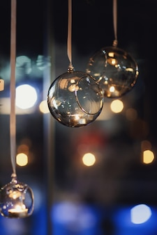 Bolas de vidro com velas pendem antes da janela