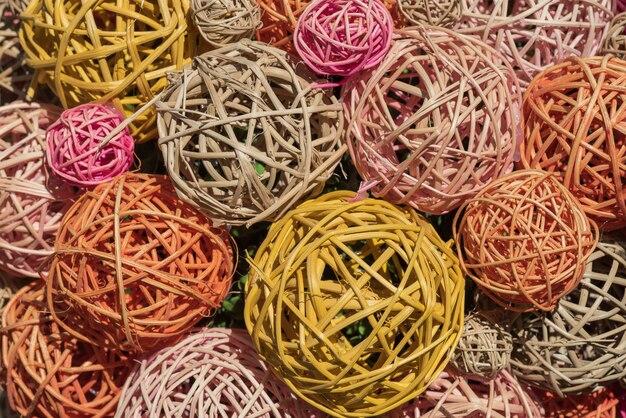 Bolas decorativas multi-coloridas de bambu de vime, fundo colorido.