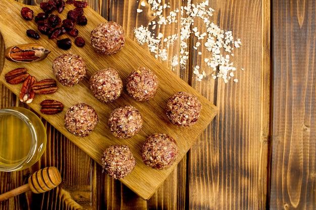 Bolas energéticas com cranberry seco e ingredientes na tábua de corte