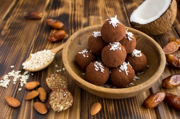 Bolas energéticas com lascas de coco, amêndoas, cereais de aveia e tâmaras na tigela marrom da madeira