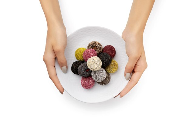 Bolas energéticas de doces veganos coloridos em um prato com as mãos da mulher isoladas