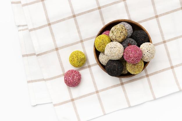 Bolas energéticas de doces veganos coloridos em um prato sobre uma mesa branca