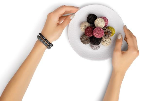 Bolas energéticas de doces veganos em um prato com as mãos da mulher isoladas em branco