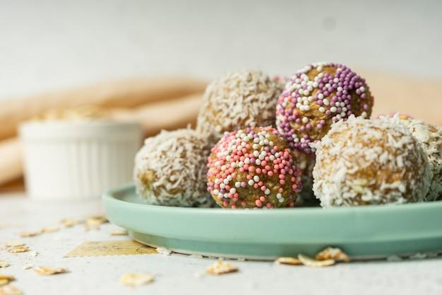 Bolas energéticas, flocos de aveia inteira e coco em pó, doces de baixa caloria, em um espaço leve