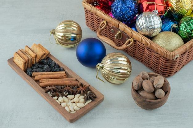Bolas festivas de natal com placa de madeira de paus de canela, anis estrelado em fundo branco. foto de alta qualidade
