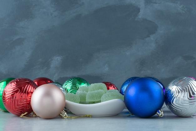 Bolas festivas de natal com prato branco cheio de geleia verde. foto de alta qualidade