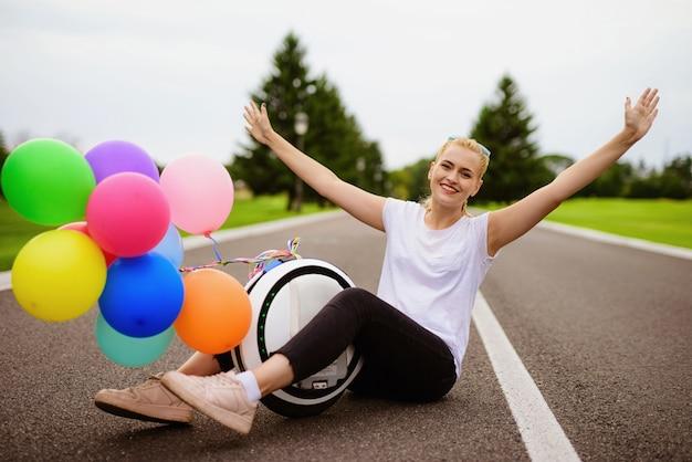 Bolas infláveis. mulher senta-se com monowheel na estrada.
