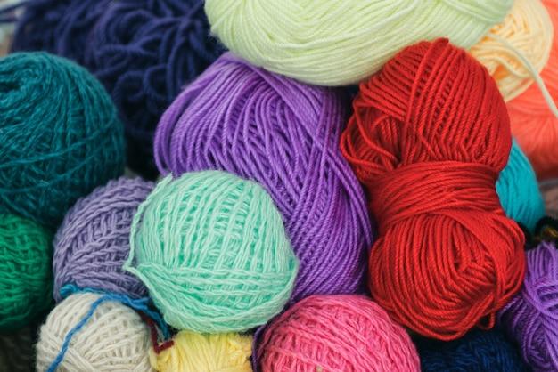 Bolas multicoloridas de fios de lã para tricô, close-up, plano de fundo