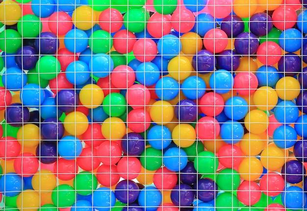 Bolas plásticas coloridas na gaiola no campo de jogos das crianças.