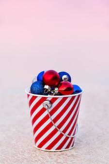 Bolas vermelhas, azuis e brancas coletadas em balde listrado ao pôr do sol para a decoração de natal