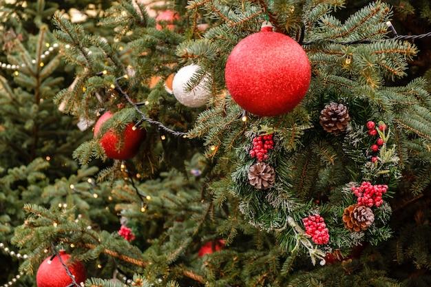 Bolas vermelhas de ano novo e guirlanda em galhos de uma árvore de natal natural ao ar livre em dia de inverno