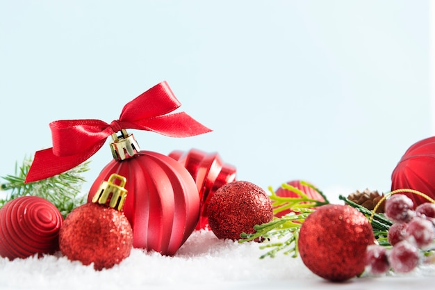 Bolas vermelhas de natal, enfeites na neve, com fita vermelha isolada.