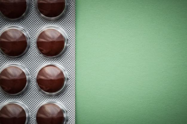 Bolha com comprimidos marrons sobre um fundo verde.