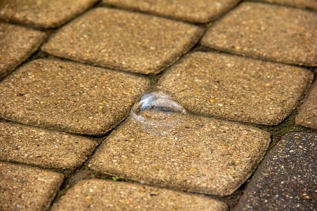 Bolha de água em uma poça depois da chuva sobre o close-up de paralelepípedos