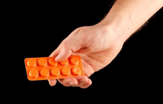Bolha de medicamento em comprimidos na mão, isolado no preto