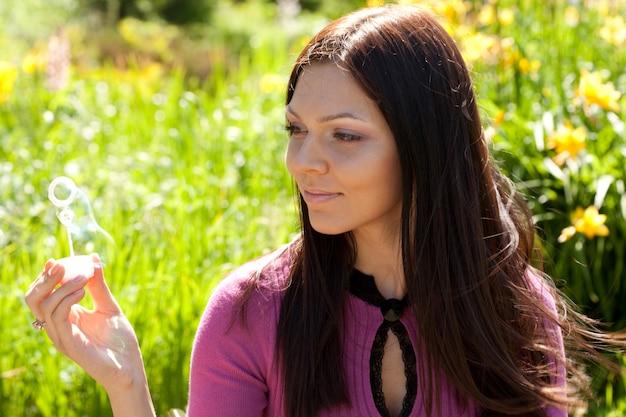 Bolha de sabão de sopro de menina contra uma grama de fundo