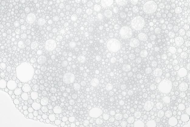Bolhas da espuma do sabão ou do champô que lavam no fundo branco.