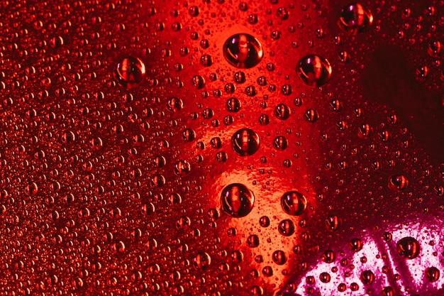 Bolhas de água sobre o plano de fundo texturizado vermelho