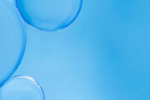 Bolhas de ar em fluido no azul fundo desfocado