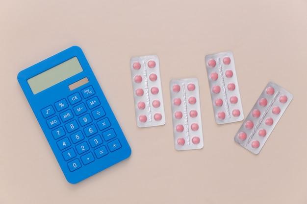Bolhas de comprimidos e calculadora em um fundo bege. vista do topo