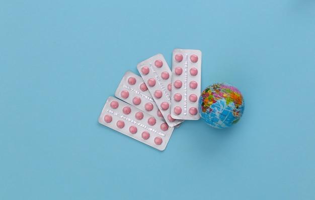 Bolhas de comprimidos e globo sobre um fundo azul. vista do topo