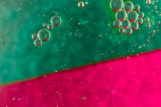 Bolhas de óleo em forma de esfera flutuando na superfície da água de cor verde e vermelho