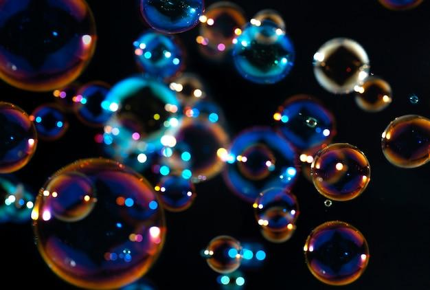 Bolhas de sabão coloridas flutuam no escuro