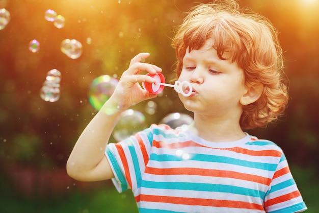 Bolhas de sabão de sopro da criança no parque do verão.