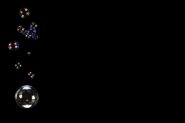 Bolhas de sabão isoladas em um fundo preto. copie o espaço.
