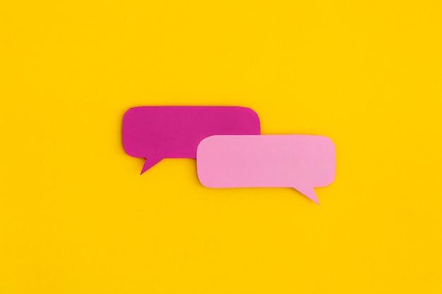 Bolhas do discurso de papel sobre um fundo amarelo. vista superior com espaço de cópia. postura plana.