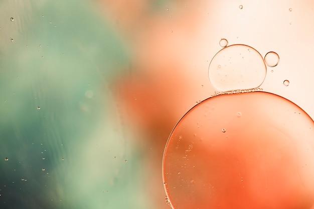 Bolhas oleosas de close-up e gotas no cenário aquoso colorido