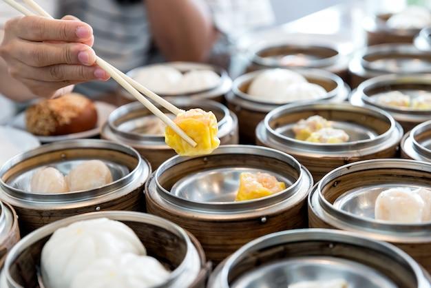 Bolinha de massa fluída chinesa na cesta de bambu na tabela no restaurante chinês.