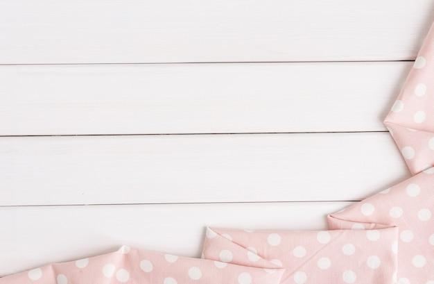 Bolinhas rosa claras dobradas toalha de mesa sobre mesa de madeira branqueada. imagem da vista superior. copyspace