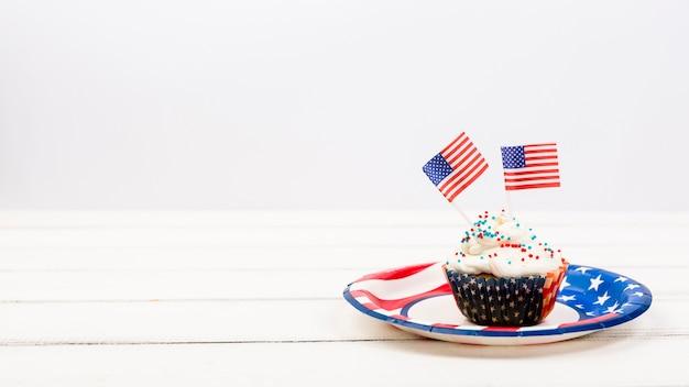 Bolinho apetitoso no prato com bandeiras americanas
