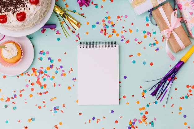 Bolinho; bolo; caixas de presente; sopradores de chifre; bloco de notas espiral em branco e confetes em fundo azul